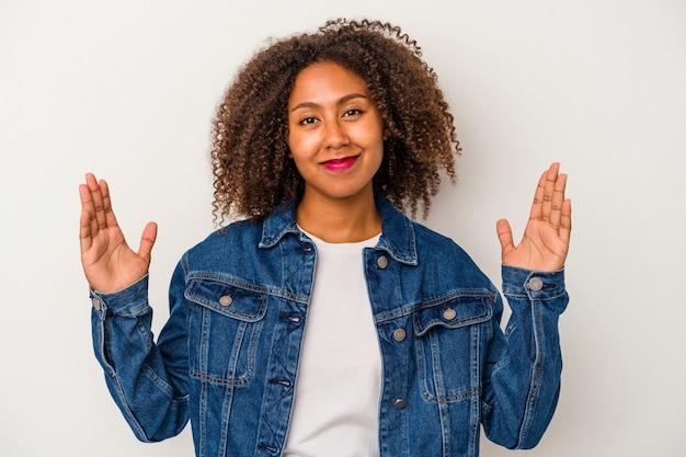 Junge afroamerikanerin mit lockigem haar isoliert auf weißem hintergrund, die etwas kleines mit den zeigefingern hält, lächelnd und selbstbewusst.