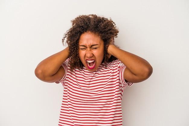 Junge afroamerikanerin mit lockigem haar isoliert auf weißem hintergrund, die ohren mit händen bedeckt und versucht, nicht zu laut zu hören.