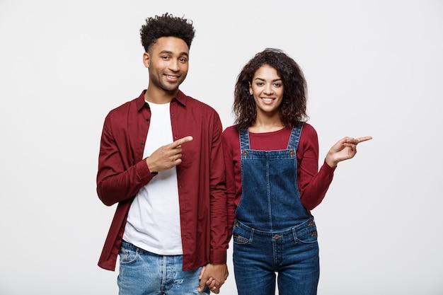 Junge afroamerikanerleute in der zufälligen kleidung, die weg schauen und zeigen finger.