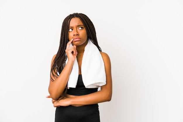 Junge afroamerikanersportfrau lokalisierte mit zweifelhaftem und skeptischem ausdruck seitlich schauen.