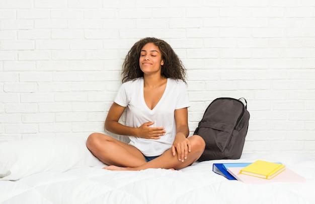Junge afroamerikanerstudentenfrau auf dem bett berührt bauch, lächelt leicht und isst und zufriedenheitskonzept.
