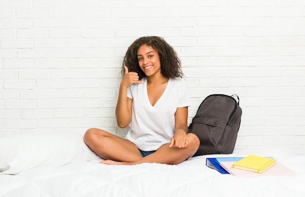 Junge afroamerikanerstudentenfrau auf dem bett, das eine handyanrufgeste mit den fingern zeigt.