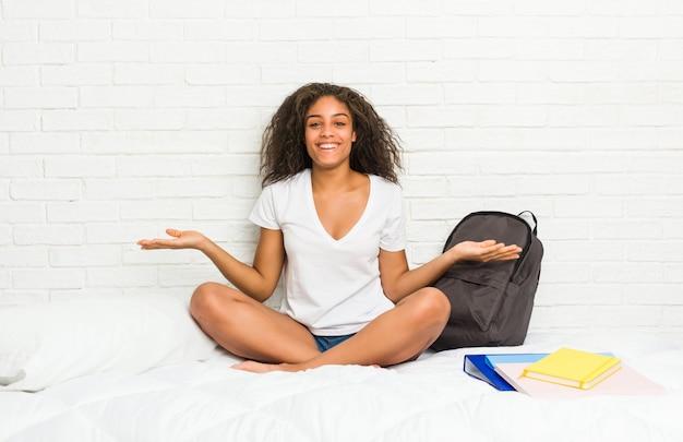 Junge afroamerikanerstudentenfrau auf dem bett, das einen willkommenen ausdruck zeigt.