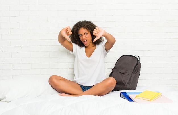 Junge afroamerikanerstudentenfrau auf dem bett, das unten daumen zeigt und abneigung ausdrückt.