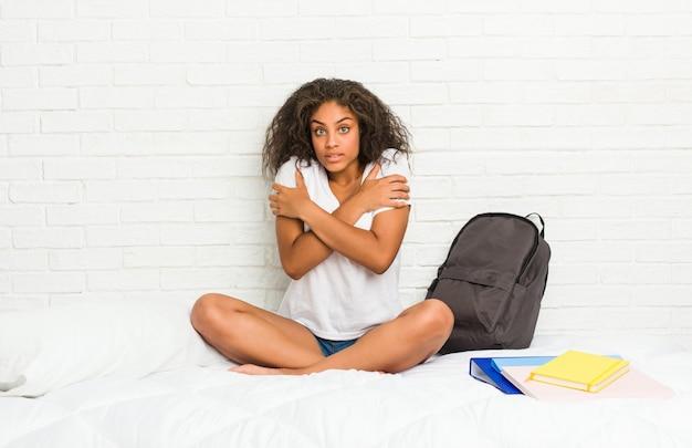 Junge afroamerikanerstudentenfrau auf dem bett, das wegen der niedrigen temperatur oder einer krankheit kalt geht.