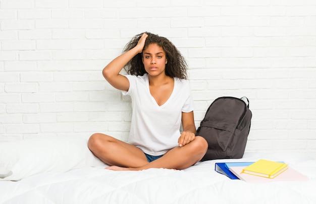 Junge afroamerikanerstudentenfrau auf dem bett ermüdete und sehr schläfrig, hand auf kopf halten.