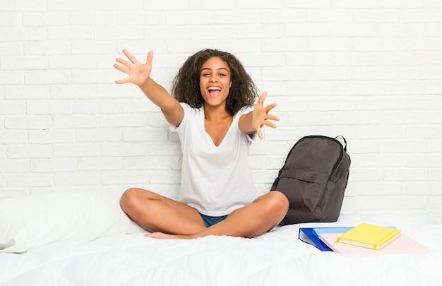 Junge afroamerikanerstudentenfrau auf dem bett fühlt sich überzeugt, der kamera eine umarmung gebend.