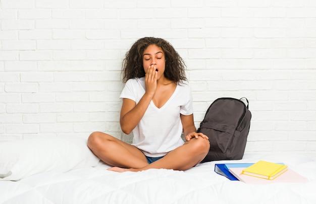 Junge afroamerikanerstudentenfrau auf dem bett gähnend, einen müden gestenbedeckungsmund mit der hand zeigend.
