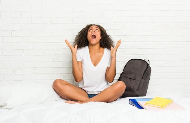Junge afroamerikanerstudentenfrau auf dem bett schreiend zum himmel, oben schauend, frustriert.