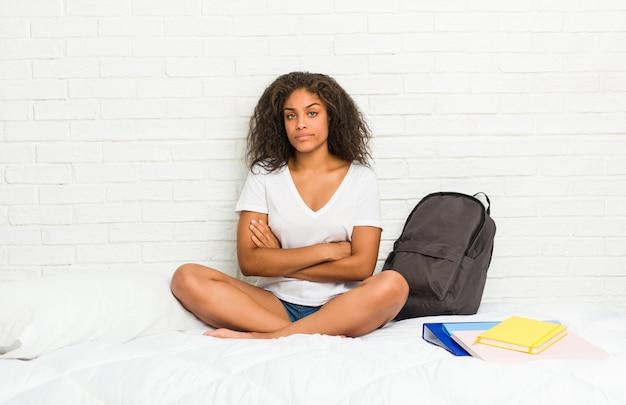 Junge afroamerikanerstudentenfrau auf dem bett unglückliches lookingwith sarkastischem ausdruck.