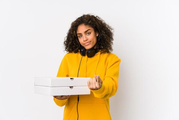 Junge afroamerikanerstudentenfrau, welche die pizzen zeigen mit dem finger auf sie hält, als ob die einladung näher kommen.