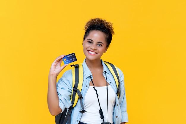 Junge afroamerikanertouristin, die lächelt und kreditkarte zeigt