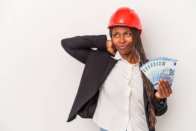 Junge afroamerikanische architektin, die rechnungen isoliert auf weißem hintergrund hält, die den hinterkopf berührt, nachdenkt und eine wahl trifft.