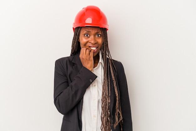 Junge afroamerikanische architektin isoliert auf weißem hintergrund beißende fingernägel, nervös und sehr ängstlich.