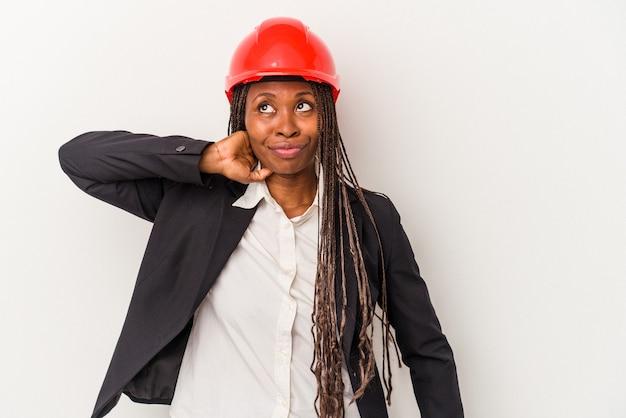 Junge afroamerikanische architektin isoliert auf weißem hintergrund, die den hinterkopf berührt, denkt und eine wahl trifft.
