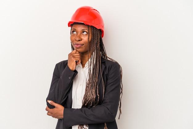 Junge afroamerikanische architektin isoliert auf weißem hintergrund, die seitlich mit zweifelhaftem und skeptischem ausdruck schaut.
