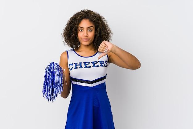 Junge afroamerikanische cheerleaderin, die eine abneigungsgeste zeigt, daumen nach unten