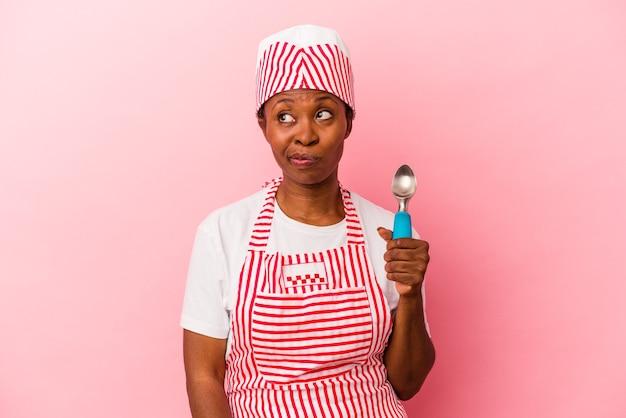 Junge afroamerikanische eiscremeherstellerin, die schaufel einzeln auf rosafarbenem hintergrund hält, verwirrt, fühlt sich zweifelhaft und unsicher.