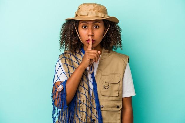 Junge afroamerikanische fischerin, die ein netz isoliert auf blauem hintergrund hält, ein geheimnis hält oder um stille bittet.