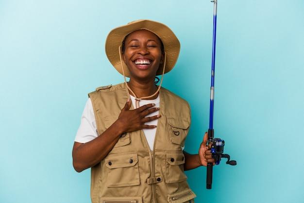 Junge afroamerikanische fischerin, die eine auf blauem hintergrund isolierte stange hält, lacht laut und hält die hand auf der brust.
