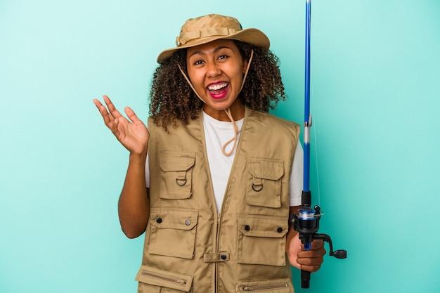 Junge afroamerikanische fischerin, die eine auf blauem hintergrund isolierte stange hält und eine angenehme überraschung empfängt, aufgeregt und die hände hebt.
