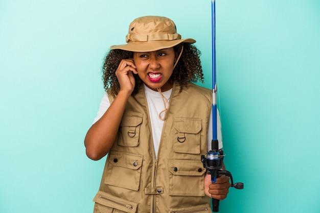 Junge afroamerikanische fischerin, die eine stange auf blauem hintergrund isoliert hält und die ohren mit den händen bedeckt.