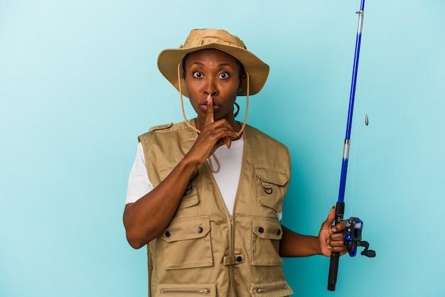 Junge afroamerikanische fischerin, die stange auf blauem hintergrund isoliert hält, ein geheimnis hält oder um stille bittet.
