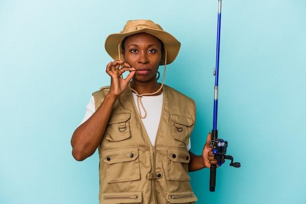 Junge afroamerikanische fischerin, die stange auf blauem hintergrund mit fingern auf den lippen hält, die ein geheimnis halten.