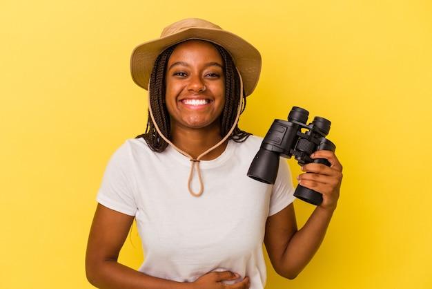 Junge afroamerikanische forscherin, die ein fernglas auf gelbem hintergrund hält, lacht und spaß hat.