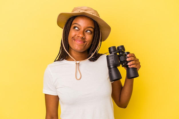 Junge afroamerikanische forscherin, die ein fernglas auf gelbem hintergrund hält und davon träumt, ziele und zwecke zu erreichen