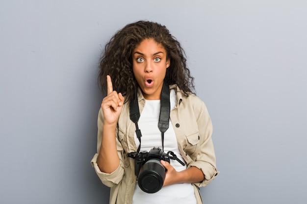 Junge afroamerikanische fotograffrau, die eine kamera hält, die einige große idee, konzept der kreativität hat.