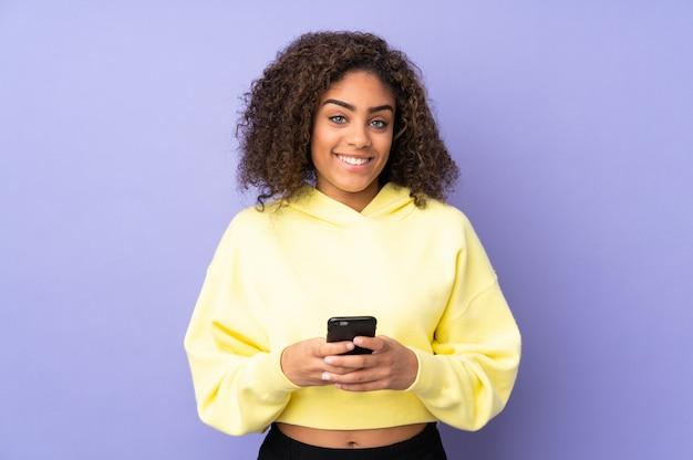 Junge afroamerikanische frau an der wand, die eine nachricht mit dem handy sendet