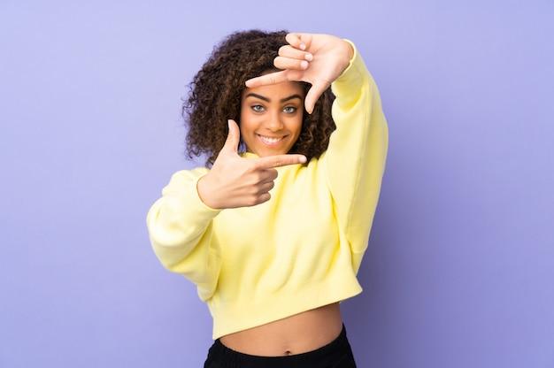 Junge afroamerikanische frau an der wand, die gesicht fokussiert. rahmensymbol