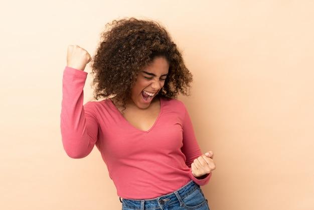 Junge afroamerikanische frau auf beige wand, die einen sieg feiert