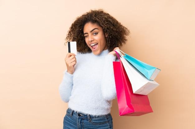 Junge afroamerikanische frau auf beige wand, die einkaufstaschen und eine kreditkarte hält
