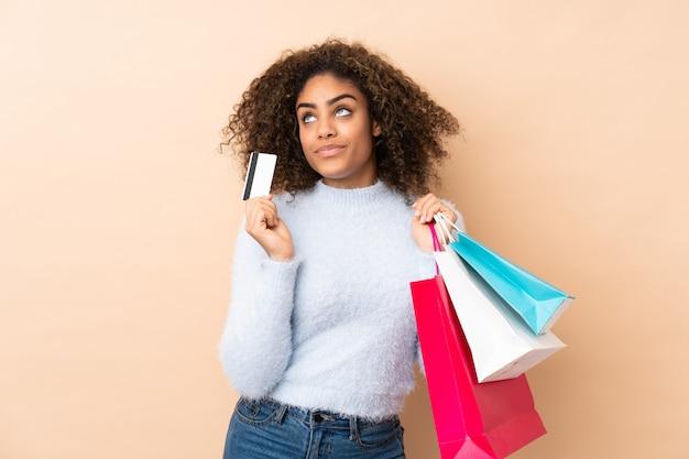Junge afroamerikanische frau auf beige wand, die einkaufstaschen und eine kreditkarte und denken hält