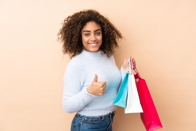 Junge afroamerikanische frau auf beige wand, die einkaufstaschen und mit daumen oben hält