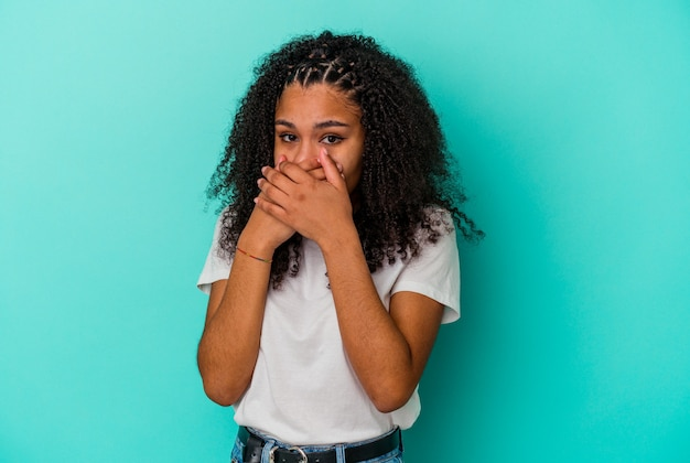Junge afroamerikanische frau auf blauem hintergrund isoliert, die den mund mit den händen bedeckt, die besorgt aussehen.
