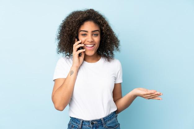 Junge afroamerikanische frau auf blauer wand, die ein gespräch mit dem handy mit jemandem hält