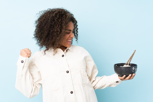 Junge afroamerikanische frau auf blauer wand, die einen sieg feiert, während eine schüssel nudeln mit essstäbchen hält