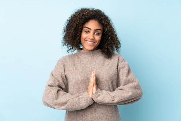 Junge afroamerikanische frau auf blauer wand hält handfläche zusammen.