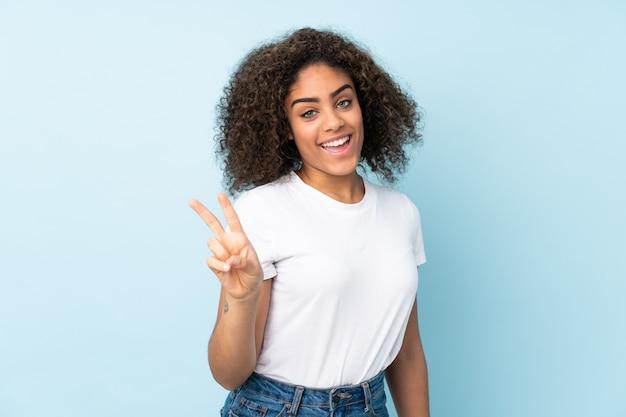 Junge afroamerikanische frau auf der blauen wand lächelnd und siegeszeichen zeigend