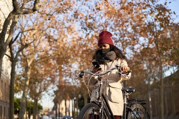 Junge afroamerikanische frau auf ihrem fahrrad unter verwendung ihres smartphones. sie trägt winterkleidung und ist in einer stadt mit herbstwetter.