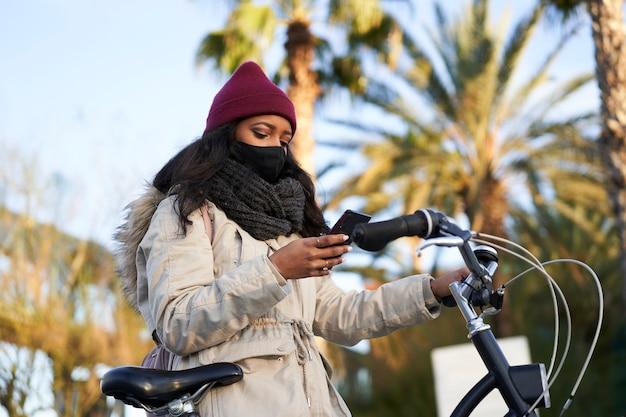 Junge afroamerikanische frau auf ihrem fahrrad, winterkleidung tragend, mit ihrem smartphone.