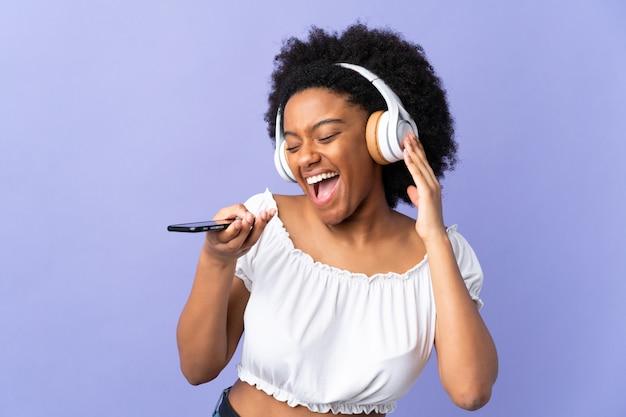 Junge afroamerikanische frau auf lila wand, die musik mit einem handy und gesang hört