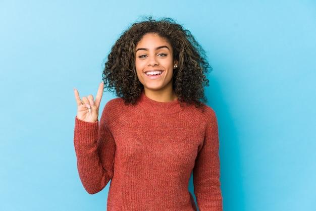 Junge afroamerikanische frau des lockigen haares, die eine hörnergeste als ein revolutionskonzept zeigt.