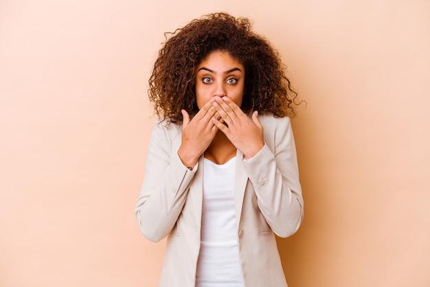 Junge afroamerikanische frau, die auf beigem hintergrund isoliert ist, schockiert, den mund mit den händen zu bedecken.
