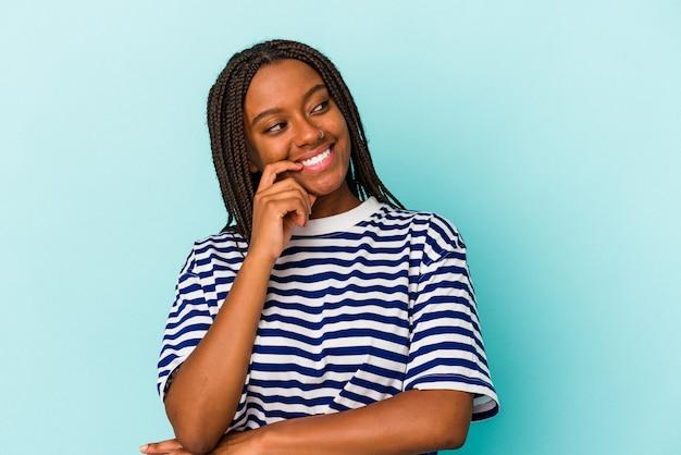 Junge afroamerikanische frau, die auf blauem hintergrund isoliert ist, entspannte sich beim nachdenken über etwas, das einen kopienraum betrachtet.