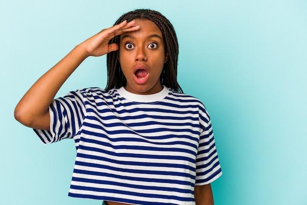 Junge afroamerikanische frau, die auf blauem hintergrund isoliert ist, schreit laut, hält die augen geöffnet und die hände angespannt.