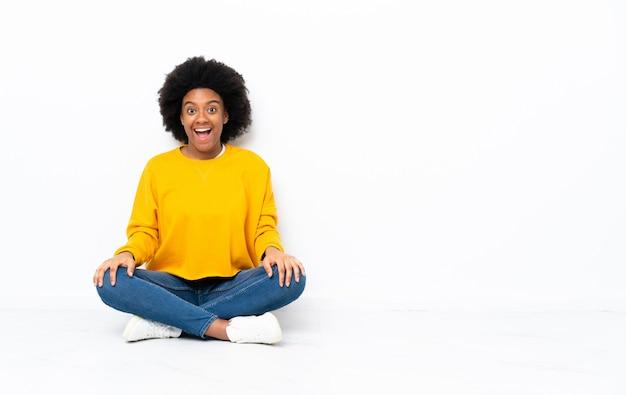 Junge afroamerikanische frau, die auf dem boden mit überraschendem gesichtsausdruck sitzt